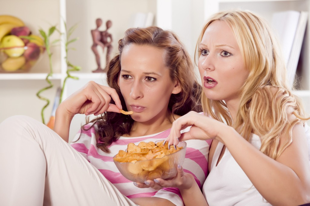 women eating snacks high in trans fats like chips